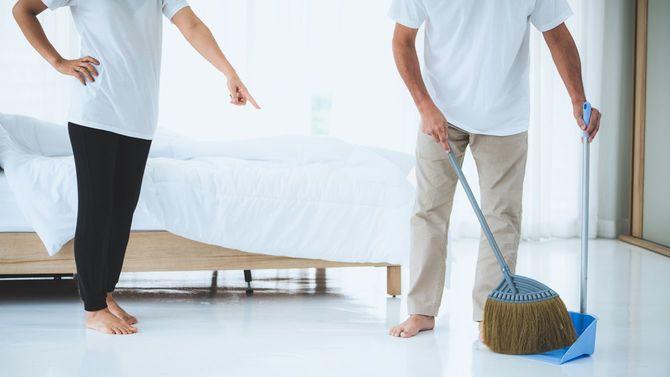 寝室を掃除するシニアのカップル