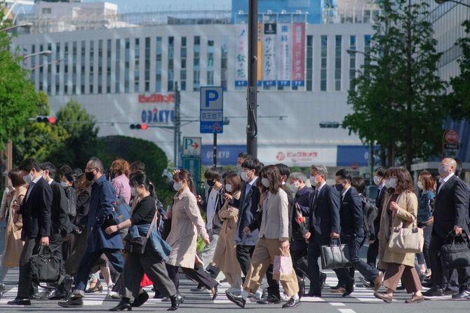 都市部の横断歩道を渡る大勢の通勤者