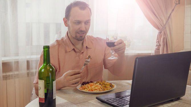 オンライン飲み会中の男性、ワイングラスをノートパソコンにかかげている