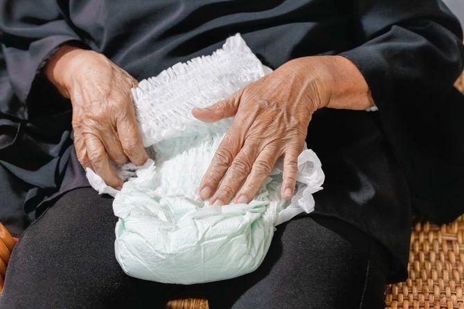 服の上からオムツをあてがって見せるシニア女性