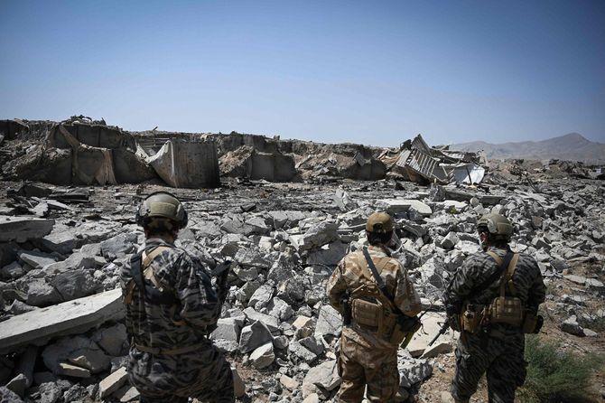 米国が同国から全軍を撤退させた後、破壊された米中央情報局(CIA)基地の瓦礫の中を歩くタリバン・バドリ313軍団のメンバー=2021年9月6日、カブール北東部のデサブズ地区