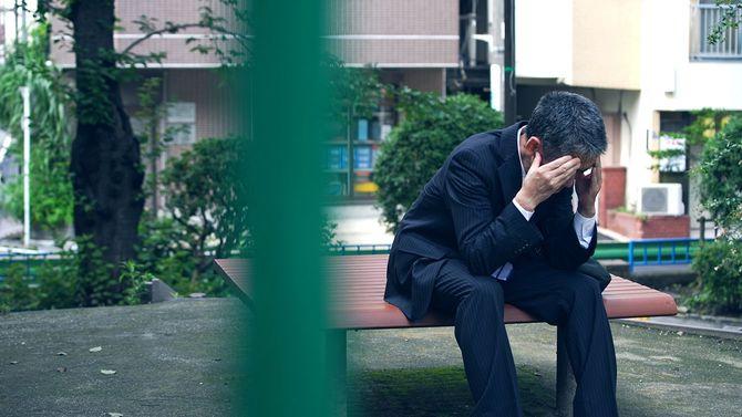 ベンチに座っている落ち込んだアジアの実業家