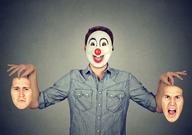 怒りと悲しみを表現する2つの顔を持つ幸せなピエロマスクの男