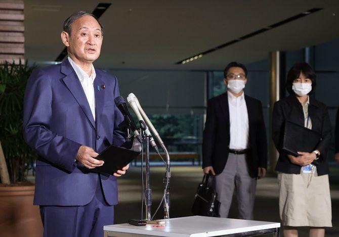 新型コロナウイルス感染拡大を受け、記者団の質問に答える菅義偉首相(左)=2021年8月13日午後、首相官邸