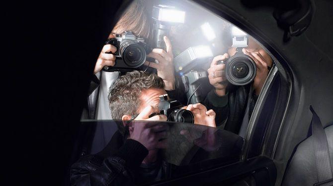 パパラッチが車に群がって写真を撮る