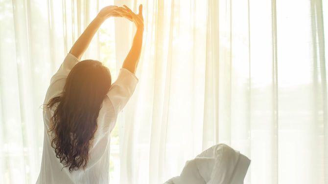 ベッドの上で、朝陽を浴びながらストレッチする女性