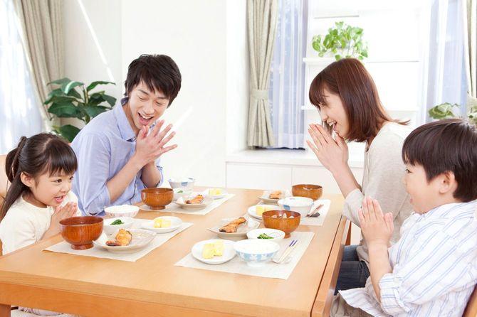 テーブルを囲み朝食の挨拶をする家族