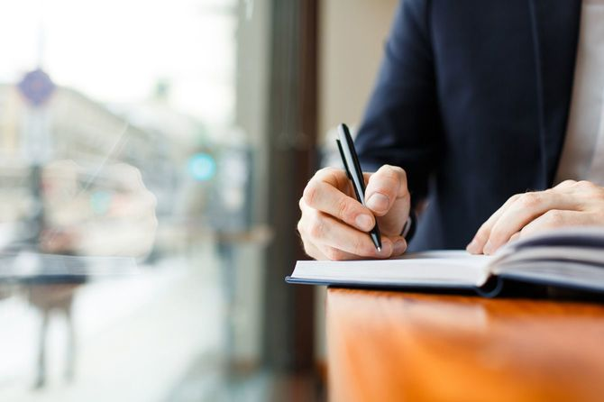 Businessman Writing in Planner at Cafe Window