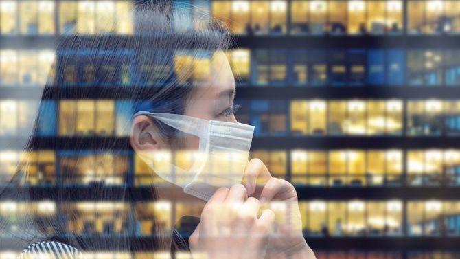 仕事に戻ろうとマスクを着けなおす女性が映る窓に、オフィスビルも写り込んでいる