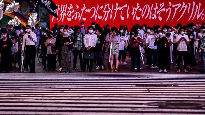 2020年7月18日、フェイスマスクをつけた人々が渋谷のスクランブル交差点で信号待ちをしている。