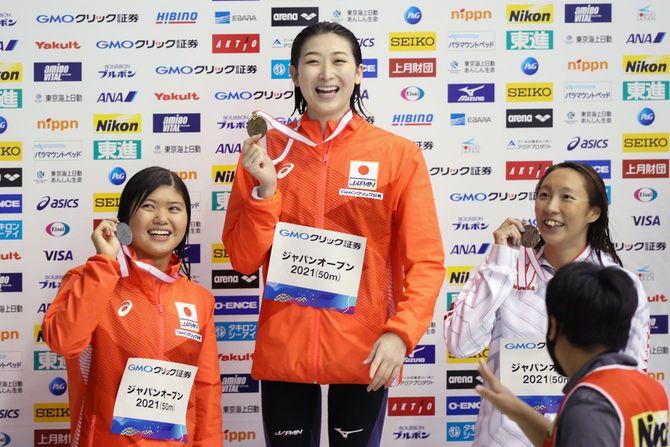 女子100メートルバタフライで優勝し笑顔を見せる池江璃花子(中央、ルネサンス)。左は2位の長谷川涼香(東京ドーム)、右は3位の相馬あい(ミキハウス)=6日、千葉県国際総合水泳場