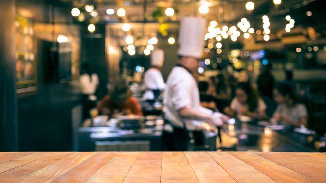 バー付きのレストランのシェフがフライパンを振っている