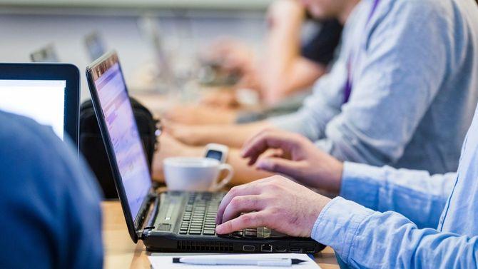 会議やセミナー中にノートパソコンでタイピングをしているビジネスマンの手