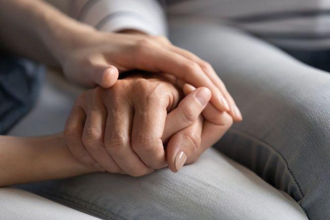 高齢女性の手を握る若い女性の手