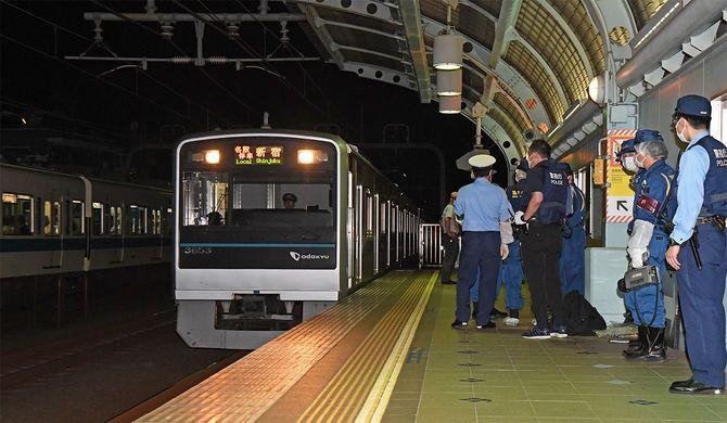 小田急線車内で6日、乗客が刃物で切られた事件で、ホームを調べる警察官ら=2021年8月7日未明、東京都世田谷区(後方は、運転再開され、新たに運行される車両)