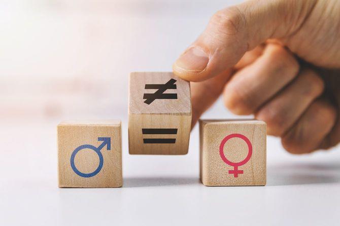 男女平等と差別の概念―記号付きの木製ブロックを手で置く