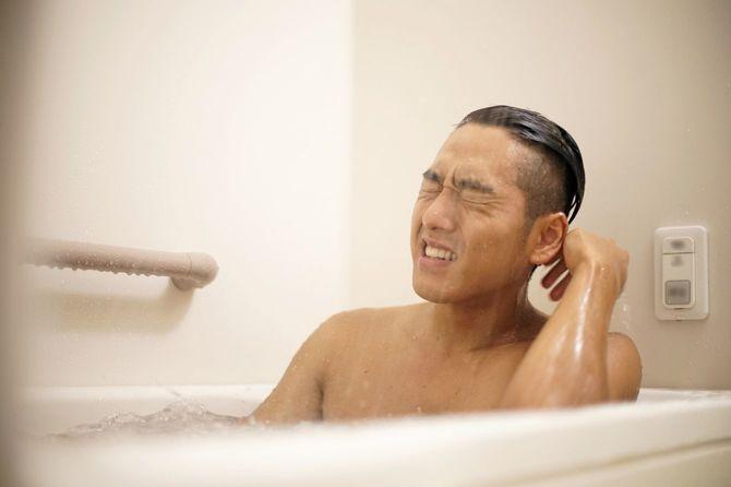 湯船に浸かりながら顔にシャワーを浴びる若い男