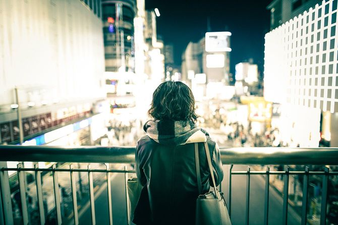 都会の夜景を眺めている若い女性