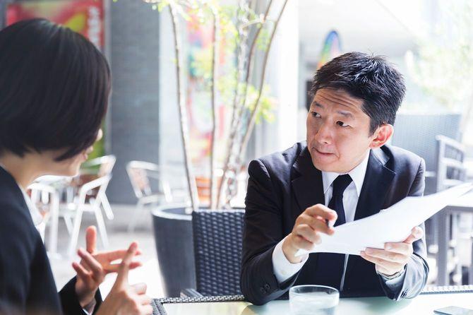 日本人経営者がクライアントの女性と業務契約の内容を詳細に話し合っている。