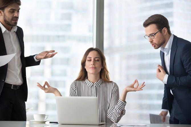 両脇で怒っている男性に注意を向けず瞑想する社員の女性