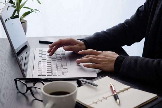 ノートパソコンを使用する男性の手元