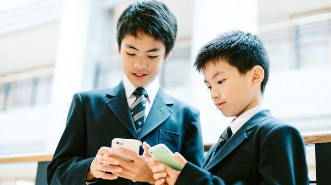 学校でスマホを使用する男子生徒たち