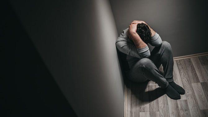 うつ病の男性が床に座り込んでしまっている