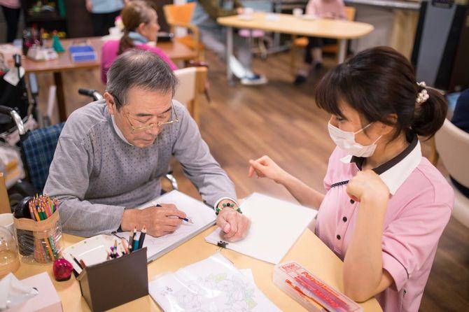 介護施設スタッフの横で絵を描く高齢男性