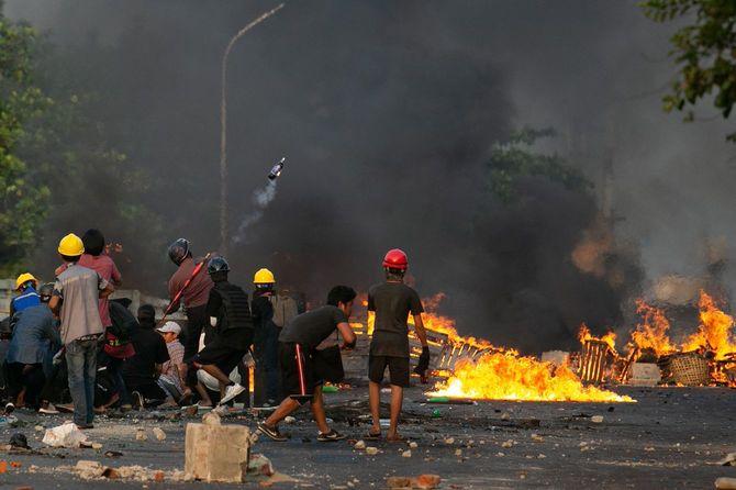 2021年3月16日、ミャンマー・ヤンゴンで行われた軍事クーデターへの抗議デモが弾圧されている。デモ参加者がガソリン爆弾を投げ、他のデモ参加者は手作りの盾の後ろに隠れて警察と対峙している。