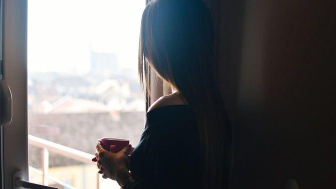 女性が一人、マグカップを手に窓の外を見つめている