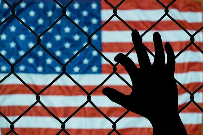 フェンスにしがみつく手とその向こうのアメリカ国旗
