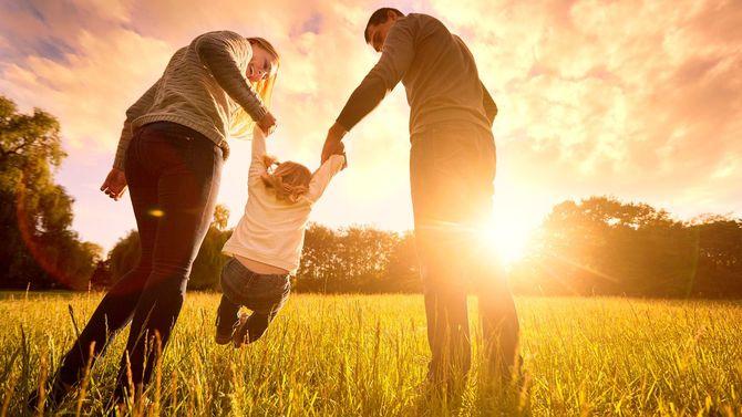 夕暮れの光の中、両親と手をつないで散歩する幼児