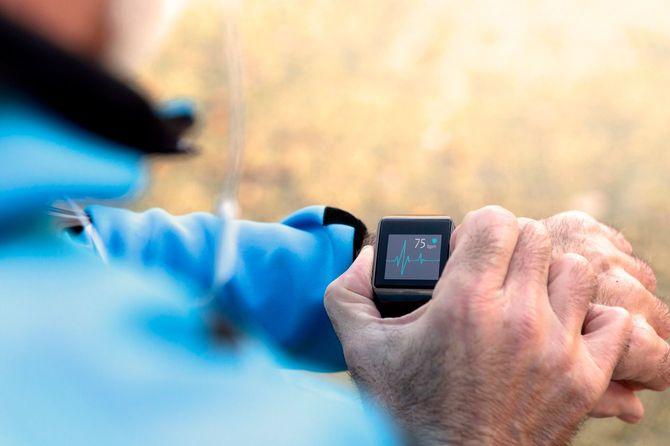 スマートウォッチで心拍数の測定をする高齢者の手