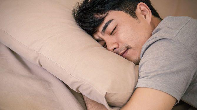 笑顔を浮かべながら腹臥位で眠る男性