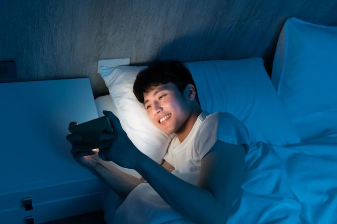暗いベッドの上でスマートフォンを操作する若い男性