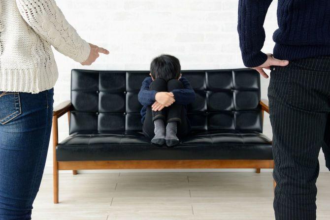 リビングルームで子供を叱る両親