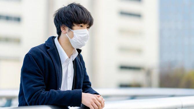 マスクを着けた、心配そうな若いビジネスマン