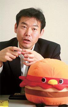長らく店舗開発・調査畑を歩み、08年3月、マーケティング部シニアリーダーに就任した齊藤雅久氏。手前は、1972年東京・板橋生まれという設定のマスコットキャラクター「モッさん」。