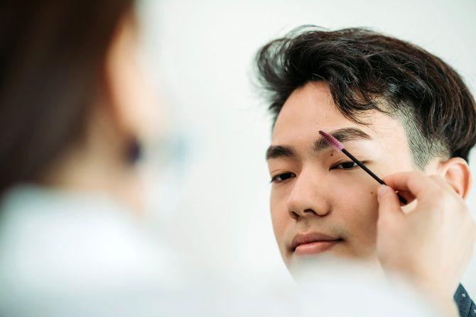 美容院で眉毛を整えてもらっているアジア人男性