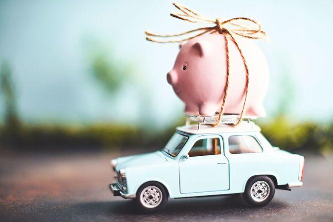 車の屋根にくくられたピンクの豚の貯金箱