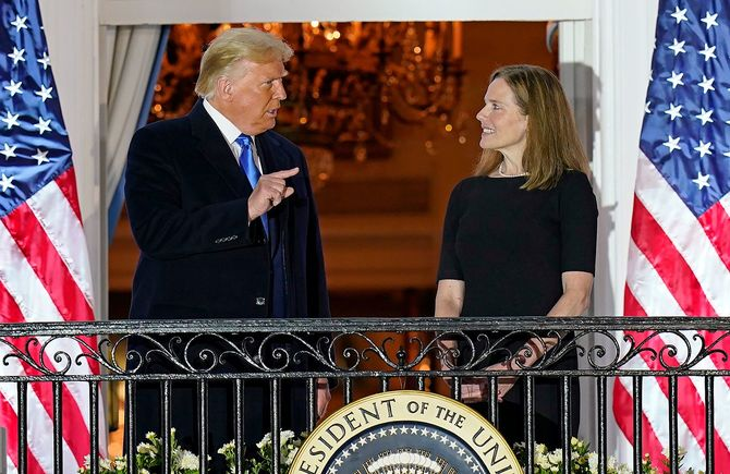 2020年10月26日、ホワイトハウスのブルールームのバルコニーで、最高裁判事に就任することを宣誓したエイミー・コニー・バレット判事(右)に向かってジェスチャーをするドナルド・トランプ米大統領(左)。
