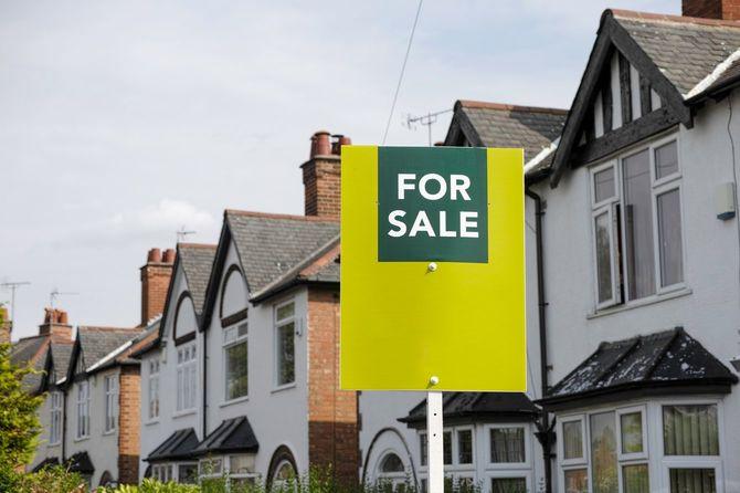 イギリスの郊外の住宅地に「For Sale」の看板を掲げた家。