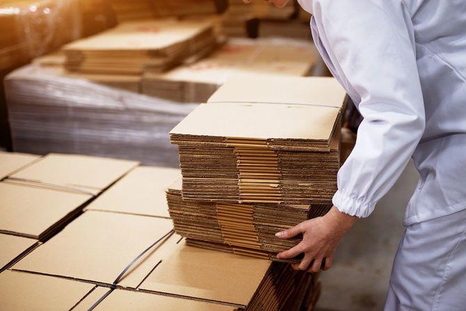 折り畳まれた段ボール箱を拾う若い女性労働者