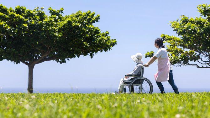 車椅子で散歩するシニアとヘルパー