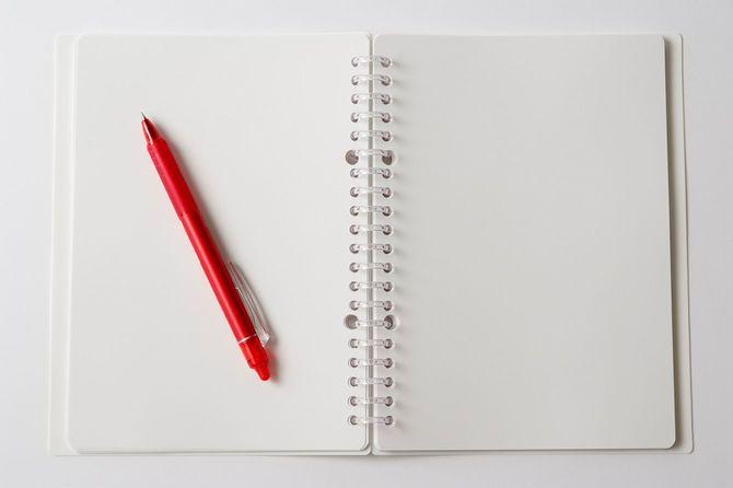 空白のスパイラルオープンペンでノートに白背景