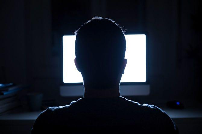 夜のコンピューターのモニターの前に座っている人
