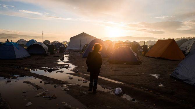 ギリシャ・イドメニの難民キャンプ。朝日を浴びる子供の眼前には数百のテントが並んでいる