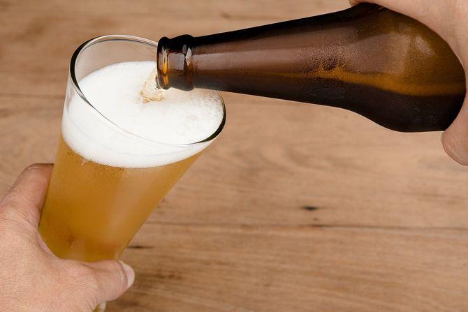 ガラス瓶からビールを注ぐ手