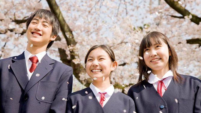 桜の花の下で笑顔を見せる高校生たち