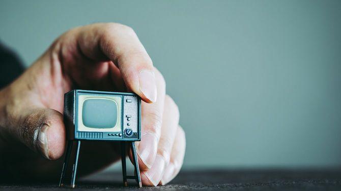 男性の手の中にテレビ